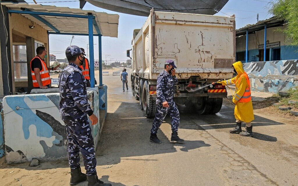 A municipal worker disinfects a truck at a checkpoint in Rafah in the southern Gaza Strip on August 31, 2020. (SAID KHATIB / AFP)