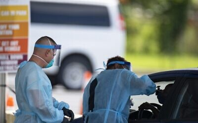 Healthcare workers takes a swab sample from a person in a car at a COVID-19 testing center outside Nissan Stadium on August 3, 2020, in Nashville, Tennessee. (Brett Carlsen/Getty Images/AFP)