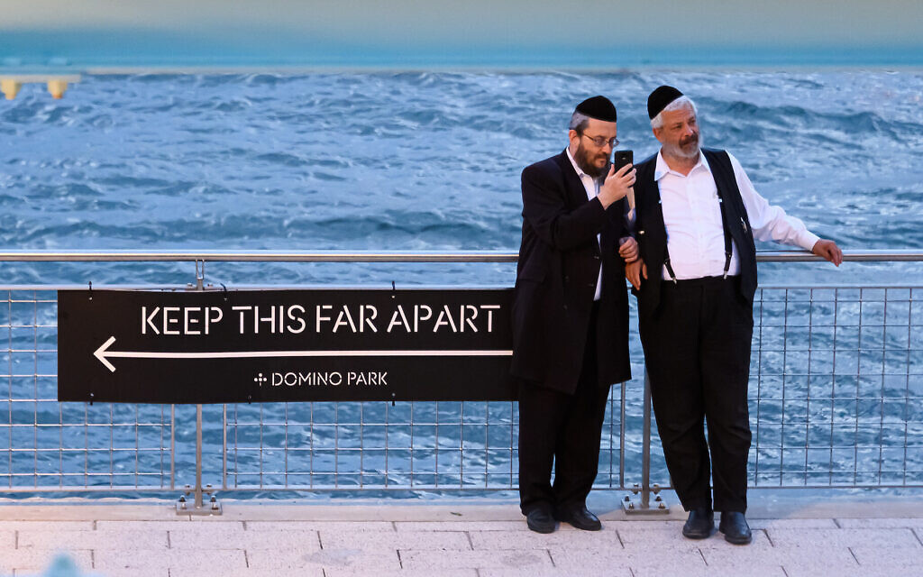 Orthodox men stand next to a social distancing sign in Williamsburg, Brooklyn, July 16, 2020. (Noam Galai/Getty Images/via JTA)