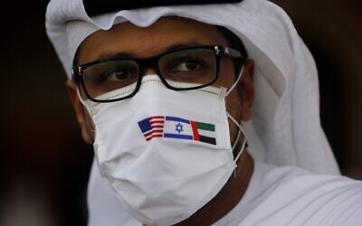 A man wearing a mask bearing the national flags of America, Israel and United Arab Emirates, watches a ceremony after an El Al plane from Israel landed in Abu Dhabi, United Arab Emirates, Aug. 31, 2020. Nir Elias/Pool via AP)