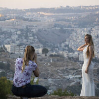 Illustrative: An Israeli woman in a wedding dress is photographed with a view of the Old City of Jerusalem in the background. (Hadas Parush/Flash90)