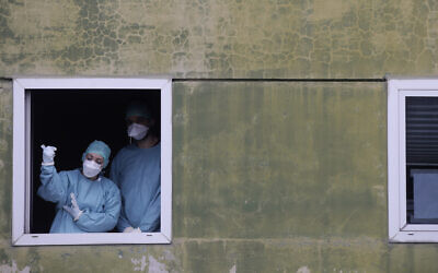 Medical staff in work at one of the emergency structures that were set up to ease procedures at the Brescia hospital, northern Italy, March 12, 2020. (AP Photo/Luca Bruno)