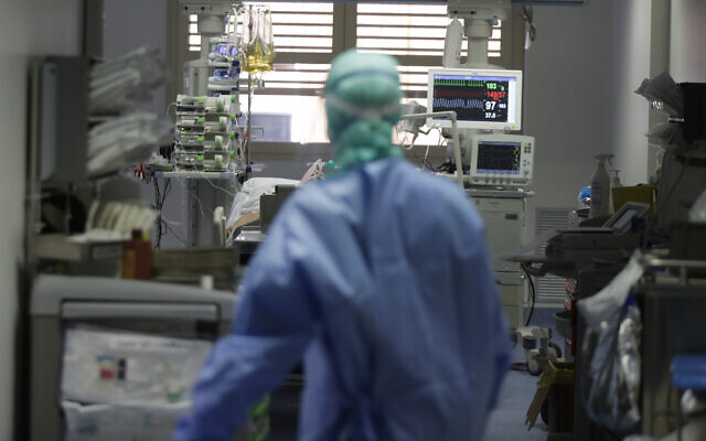 A doctor watches a coronavirus patient under treatment in the intensive care unit of the Brescia hospital in Italy, on March 16, 2020. (AP Photo/Luca Bruno)