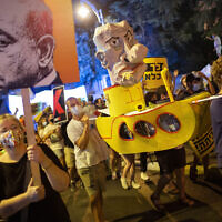 Demonstrators chant slogans and hold signs during a rally against Prime Minister Benjamin Netanyahu outside his residence in Jerusalem, Saturday, Aug 1, 2020. (AP Photo/Oded Balilty)