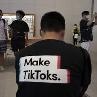 A man wearing a shirt promoting TikTok is seen at an Apple store in Beijing on Friday, July 17, 2020.(AP Photo/Ng Han Guan)