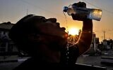 Laith Jabbar, a gas station worker, drinks water in Basra, Iraq, July. 27, 2020. (AP Photo/Nabil al-Jurani)