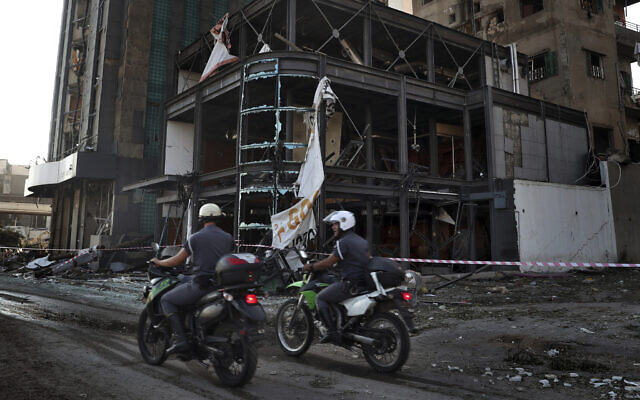 Police officers pass a damaged building near the scene of an explosion that hit the seaport of Beirut, Lebanon, August 5, 2020. (Bilal Hussein/AP)