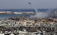 A Lebanese army helicopter drops water at the scene where an explosion hit the seaport of Beirut, Lebanon, August 5, 2020. (Hussein Malla/AP)