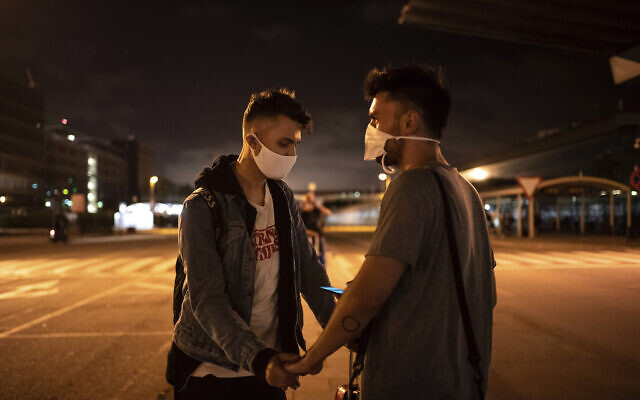 Piotr Grabarczyk and his boyfriend Kamil Pawlik, right, from Poland, wait for a taxi outside the airport after Grabarczyk arrived in Barcelona, Spain, early July 29, 2020.(AP Photo/Felipe Dana)