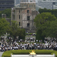 Visitors observe a minute of silence for the victims of the atomic bombing, at 8:15 a.m., the time atomic bomb exploded over the city, at the Hiroshima Peace Memorial Park during the ceremony to mark the 75th anniversary of the bombing, August 6, 2020, in Hiroshima, western Japan. (AP Photo/Eugene Hoshiko)