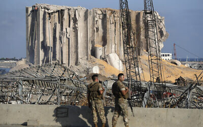 Lebanese army soldiers stand guard at the scene where an explosion hit on Tuesday the seaport of Beirut, Lebanon, Thursday, Aug. 6, 2020. (AP Photo/Hussein Malla)