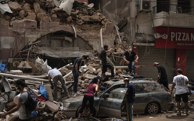People remove debris from a house damaged by Tuesday's explosion in the seaport of Beirut, Lebanon, Friday, Aug. 7, 2020 (AP Photo/Felipe Dana)