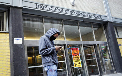 In this March 16, 2020, file photo, a pedestrian wears a face mask while standing outside the High School of Economics & Finance, closed due to coronavirus concerns, in New York (AP Photo/John Minchillo, File)