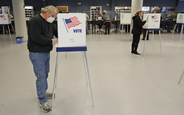 This Tuesday, April 28, 2020 file photo shows Jerome Fedor, left, voting using social distancing at the Cuyahoga County Board of Elections, in Cleveland, Ohio (AP Photo/Tony Dejak, File)