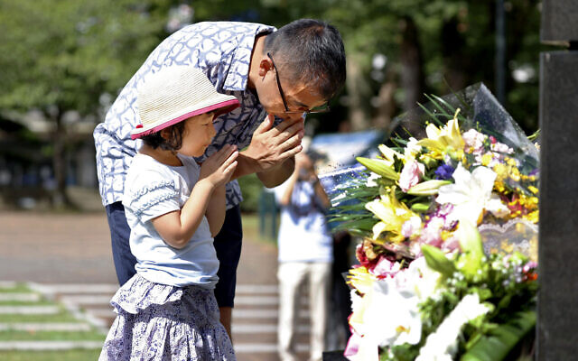 A man and his daughter pray for the victims of US atomic bombing at the Atomic Bomb Hypocenter Park in Nagasaki, southern Japan, August 9, 2020 (Takuto Kaneko/Kyodo News via AP)