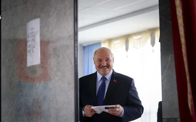 Belarusian President Alexander Lukashenko reacts as he walks to cast his ballot at a polling station during the presidential election in Minsk, Belarus, Sunday, August 9, 2020. (AP Photo/Sergei Grits)