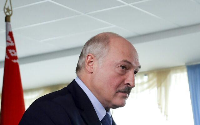Belarusian President Alexander Lukashenko after voting at a polling station with a Belarusian national flag on the left, during the presidential election in Minsk, Belarus, August 9, 2020. (AP Photo/Sergei Grits)