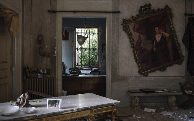 A crooked painting hangs on the wall of the Sursock Palace, heavily damaged after the explosion in the seaport of Beirut, Lebanon, Friday, August 7, 2020. (AP Photo/Felipe Dana)