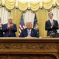 President Donald Trump, accompanied by (From left), U.S. special envoy for Iran Brian Hook, Avraham Berkowitz, Assistant to the President and Special Representative for International Negotiations, U.S. Ambassador to Israel David Friedman, President Donald Trump's White House senior adviser Jared Kushner, and Treasury Secretary Steven Mnuchin, applaud in the Oval Office at the White House, Wednesday, Aug. 12, 2020, in Washington. Trump said on Thursday that the United Arab Emirates and Israel have agreed to establish full diplomatic ties. (AP Photo/Andrew Harnik)