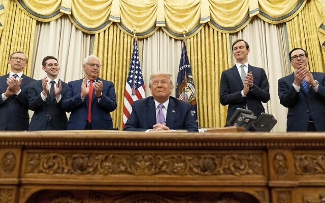 US President Donald Trump, accompanied by (From left), US special envoy for Iran Brian Hook, Avraham Berkowitz, Assistant to the President and Special Representative for International Negotiations, US Ambassador to Israel David Friedman, Trump's White House senior adviser Jared Kushner, and Treasury Secretary Steven Mnuchin, applauding in the Oval Office at the White House, August 12, 2020, in Washington. (AP Photo/Andrew Harnik)
