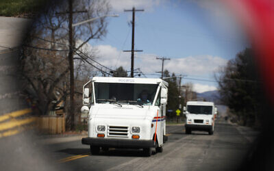 Illustrative: United States Post Office delivery trucks are reflected in the side mirror of a vehicle as postal delivers set off on their daily rounds in Arvada, Colorado, on March 31, 2020. (AP Photo/David Zalubowski, File)