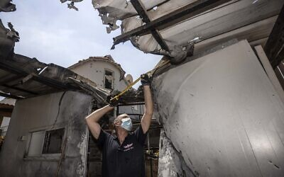 An Israeli police officer inspects the damage to a home after it was hit by a rocket fired by Palestinian militants from the Gaza Strip, in Sderot on August 16, 2020. (AP Photo/Tsafrir Abayov)