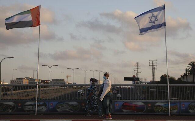Women wearing face masks against the coronavirus walk past United Arab Emirates and Israeli flags at the Peace Bridge in Netanya, Israel, August 16, 2020. (AP Photo/Ariel Schalit)