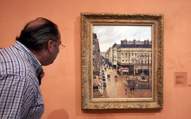 """This May 12, 2005 file photo shows a visitor viewing the Impressionist painting called """"Rue St.-Honore, Apres-Midi, Effet de Pluie"""" painted in 1897 by Camille Pissarro, on display in the Thyssen-Bornemisza Museum in Madrid. (AP Photo/Mariana Eliano, File)"""