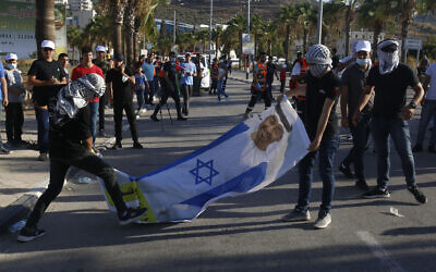 Palestinians with a banner showing Abu Dhabi Crown Prince Mohammed bin Zayed al-Nahyan wearing an Israeli flag, during a rally against the United Arab Emirates' normalization deal with Israel, in the West Bank village of Turmusaya near Ramallah, Aug. 19, 2020. (AP Photo/Majdi Mohammed)