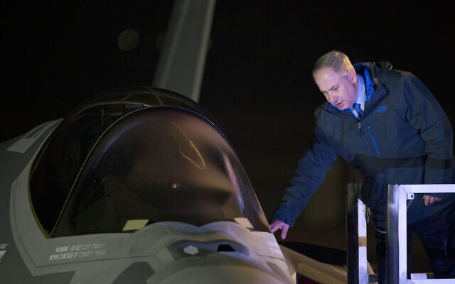 In this December 12, 2016, file photo, Prime Minister Benjamin Netanyahu reaches to one of the first two next-generation F-35 fighter jets after it landed during an unveiling ceremony upon arrival in Nevatim Air Force Base near Beersheba, Southern Israel. (AP/Ariel Schalit, File)