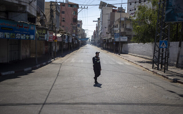 A Palestinian Hamas policeman wears a face mask as he guards in a street in Gaza City during a 48 hour lockdown imposed following the discovery of the first coronavirus cases in the Gaza Strip on August 25, 2020. (AP/Khalil Hamra)
