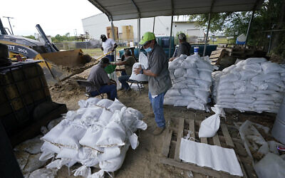 Municipal workers fill sandbags for the elderly and those with disabilities ahead of Hurricane Laura in Crowley, Louisiana, August 25, 2020. (AP Photo/Gerald Herbert)