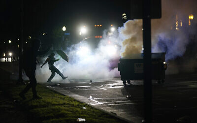 A US protester kicks a smoke canister on August 25, 2020 in Kenosha, Wisconsin. (AP Photo/Morry Gash)
