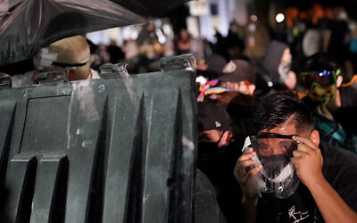 A protester takes cover during clashes outside the Kenosha County Courthouse, August 25, 2020, in Kenosha, Wisconsin. (AP Photo/David Goldman)