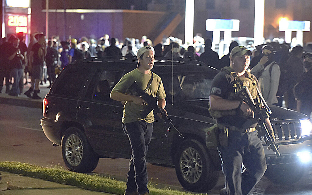 Kyle Rittenhouse, left, with backwards cap, walks along Sheridan Road in Kenosha, Wisconsin, August 25, 2020, with another armed civilian. (Adam Rogan/The Journal Times via AP)