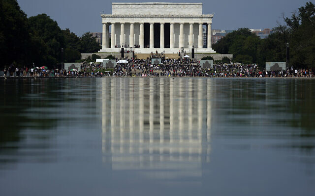 The Lincoln Memorial is reflected in the water as people gather to attend the March on Washington, Friday Aug. 28, 2020, in Washington, on the 57th anniversary of the Rev. Martin Luther King Jr.'s 'I Have A Dream' speech. (AP Photo/Carolyn Kaster)