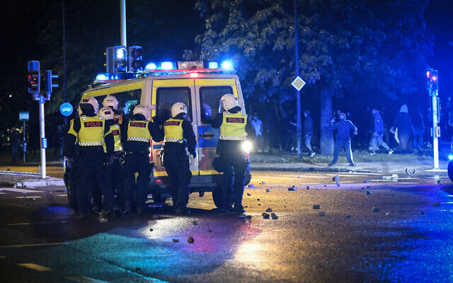 Demonstrators throw stones at police as protesters riot in the Rosengard neighborhood of Malmo, Sweden, August 28, 2020. (TT News Agency via AP)