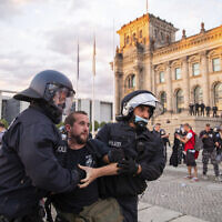 Police officers push away a crowd of demonstrators from the square 'Platz der Republik' in front of the Reichstag building during a demonstration against coronavirus restrictions in Berlin, Germany, August 29, 2020. (Christoph Soeder/dpa via AP)