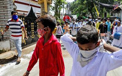 Muslims wearing face masks beat drums as they take part in a Muharram procession in Kolkata, India on August 30, 2020. (AP/ Bikas Das)