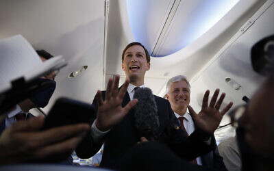 US President Donald Trump's senior adviser Jared Kushner, center, stands with US National Security Advisor Robert O'Brien while speaking to journalists during a flight on an Israeli El Al plane to Abu Dhabi, United Arab Emirates, Monday, Aug. 31, 2020. (Nir Elias/Pool Photo via AP)