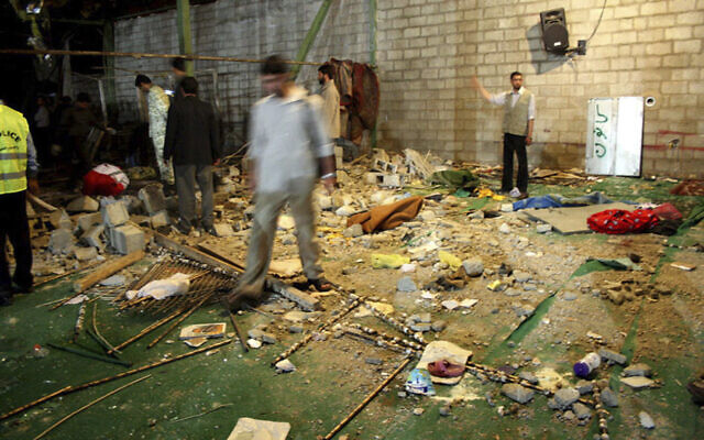 An Iranian police officer and other people look through debris  at the scene of a bomb explosion in a mosque, on April 12 2008 in Shiraz (AP photo)