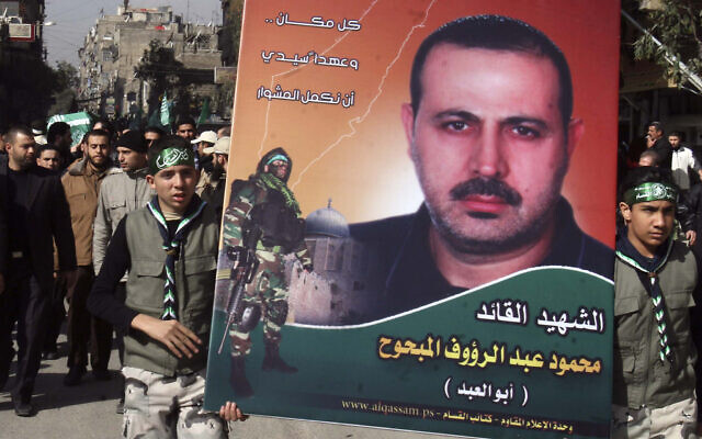 Palestinians carry a picture of Mahmoud al-Mabhouh, as others carry his coffin, left, during his funeral procession at Yarmouk, near Damascus, Syria, January 29, 2010. (AP Photo/Bassem Tellawi/File)