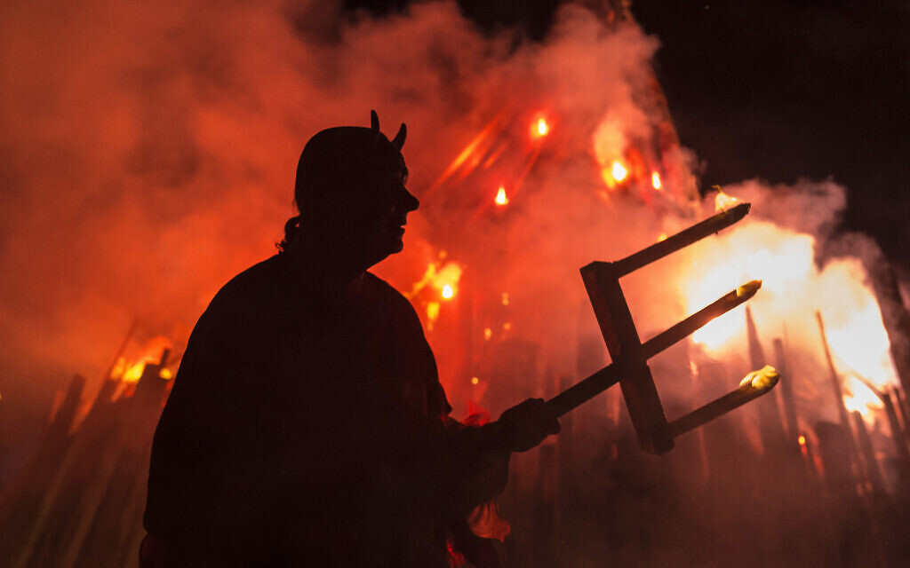 Illustrative: A man dressed as a devil performs in front of a giant fire during the Walpurgis night in Erfurt, central Germany, Sunday, April 30, 2017. (AP Photo/Jens Meyer)