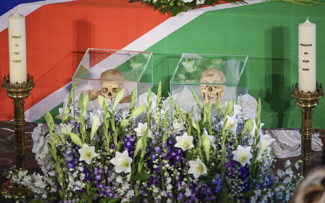 The skulls of two people killed in the  the Herero and Nama uprising between 1904 and 1908 are flanked by candles during a ceremony in Berlin, Aug. 29, 2018 before the repatriation of the remains to Namibia. (Gregor Fischer/dpa via AP)
