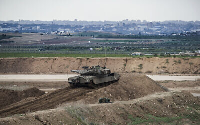 Illustrative: An Israeli tank takes position on the Israel-Gaza border. (AP Photo/Tsafrir Abayov)