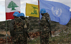 In this Thursday, December 13, 2018 photo, UN peacekeepers hold their flag while standing next to Hezbollah and Lebanese flags, at the site where Israeli excavators are working, near the southern border village of Mays al-Jabal, Lebanon. (AP/Hussein Malla)