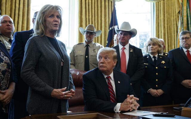 US President Donald Trump listens as Mary Ann Mendoza, who lost her son Brandon when he was killed by a drunk driver that was an undocumented immigrant, speaks before he signs the first veto of his presidency in the Oval Office of the White House, Friday, March 15, 2019, in Washington (AP Photo/Evan Vucci)
