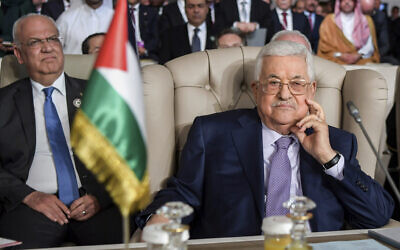 Palestinian Authority President Mahmoud Abbas, right, and secretary general of the Palestinian Liberation Organization, Saeb Erekat attend the the 30th Arab Summit in Tunis, Tunisia, Aughust 16, 2020. (Fethi Belaid/ Pool photo via AP)