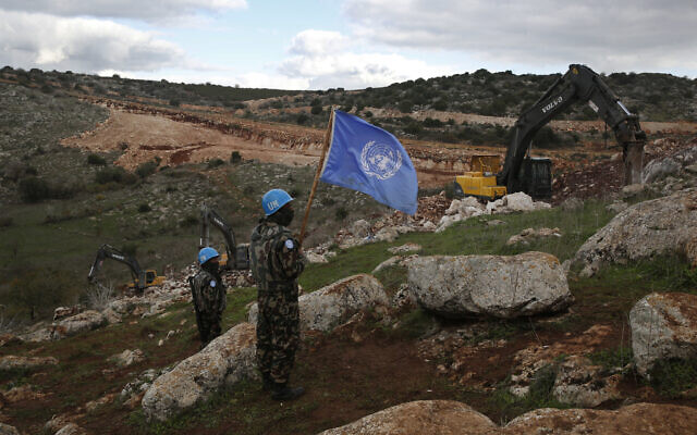 UNIFIL peacekeepers hold their flag, as they observe Israeli excavators attempt to destroy cross-border tunnels dug by Hezbollah, near the southern Lebanese-Israeli border village of Mays al-Jabal, Lebanon, December 13, 2019. (Hussein Malla/AP)