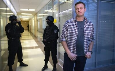 Russian opposition leader Alexei Navalny speaks to the media in front of security officers standing guard at the Foundation for Fighting Corruption office in Moscow, Russia, December 26, 2019 (AP Photo/Alexander Zemlianichenko)